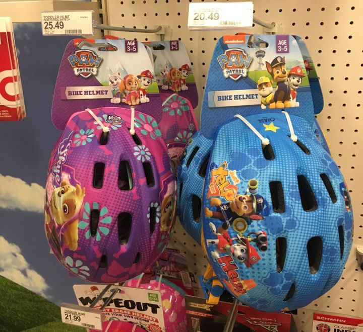 Children's bike helmets hang on the shelf, the boys blue helmet is $20.49 and the girls pink helmet is $25.49