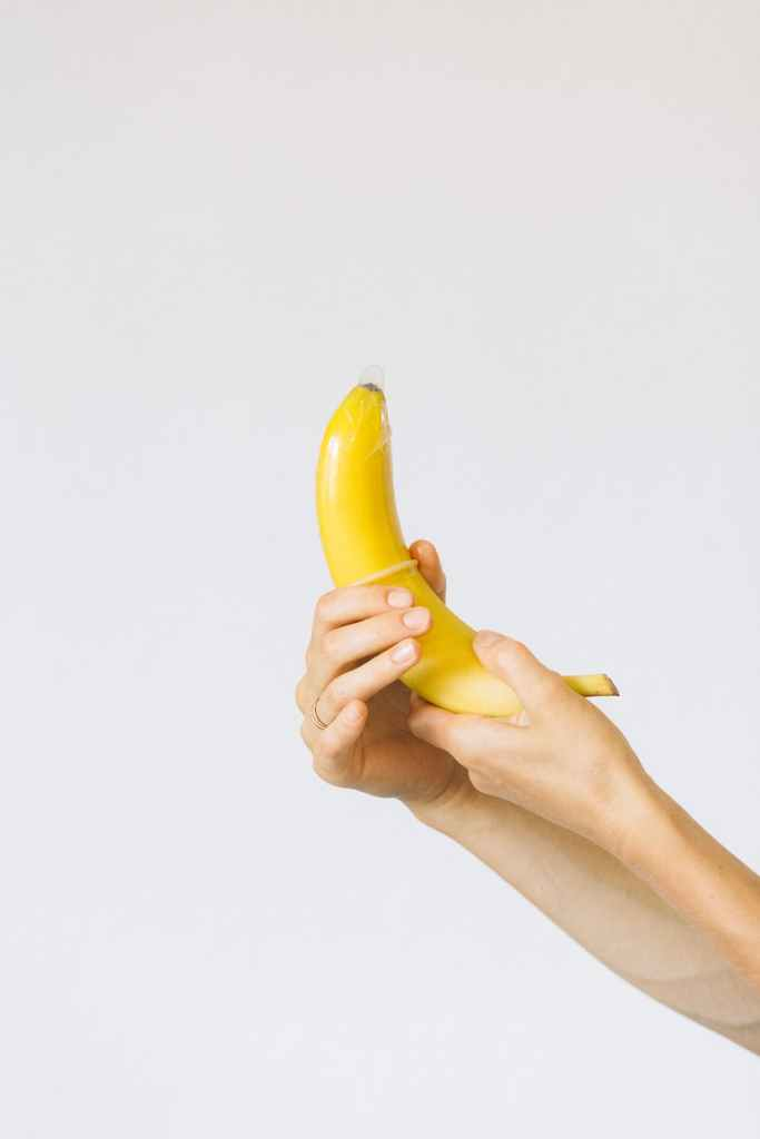 A hand putting a condom on a banana.
