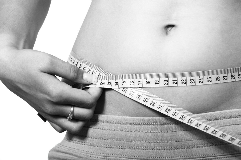 A person holding a measuring tape around their stomach.