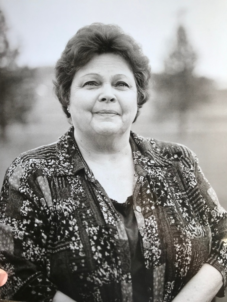 Black and white photo of the author's grandmother wearing a floral shirt and smiling at the camera