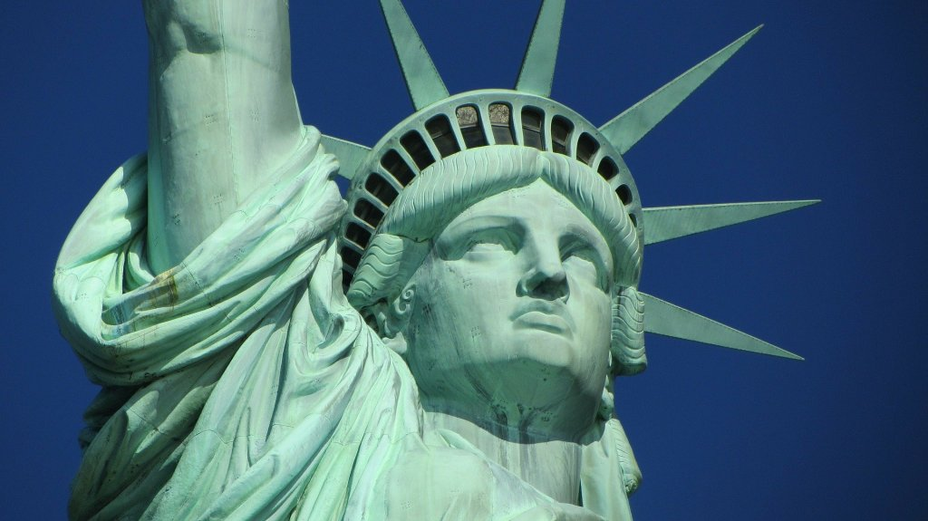 A close up photo of the Statue of Liberty with a blue sky in the back.